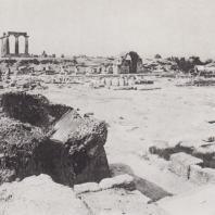 Коринф. Агора, лавки, вид с юга, со стороны трибуны. Посреди агоры фрагменты баз колонн алтаря и статуя Афины. На заднем плане святилище Аполлона. Фото: Анджей Дзевановский