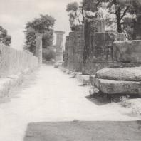 Олимпия. Герайон. Вид южной стороны с запада. Налево нижняя часть стены, так наз. ортостата, направо уцелевшие нижние части южной колоннады. В глубине реконструированные колонны восточного фасада. Фото: Анджей Дзевановский