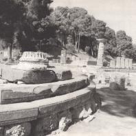 Олимпия. Филиппейон. Три ступени крепидомы вместе с базой ионической колонны перистасиса. В глубине Герайон на фоне горы Крон, вид с юго-восточной стороны. Фото: Анджей Дзевановский